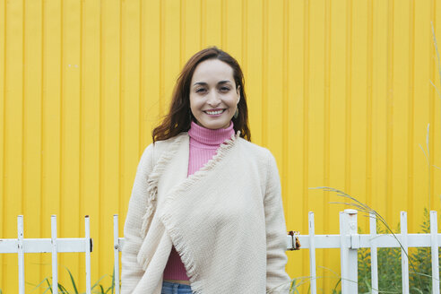 Portrait of smiling woman in front of yellow background - JUBF00183