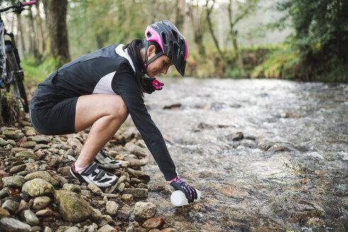 Female mountain biker filling a bottle of water in river - RAEF01668