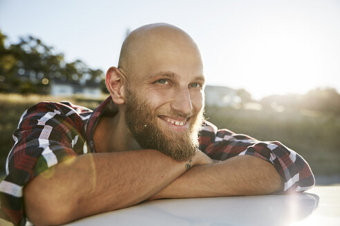 Portrait of bald young man with beard leaning on car roof - SRYF00218