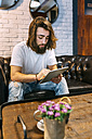 Stylish young man sitting on couch in a cafe using tablet - MGOF02812