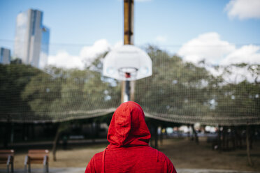 Young man wearing red hoodie on a basketball court - JRFF01163