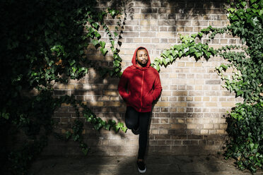 Young man wearing red hoodie leaning against a wall - JRFF01166