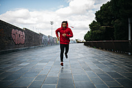 Smiling young man wearing red hoodie running in the city - JRF01169