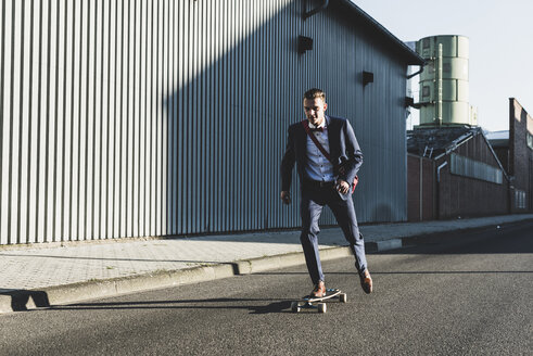 Young businessman riding skateboard on the street - UUF09822