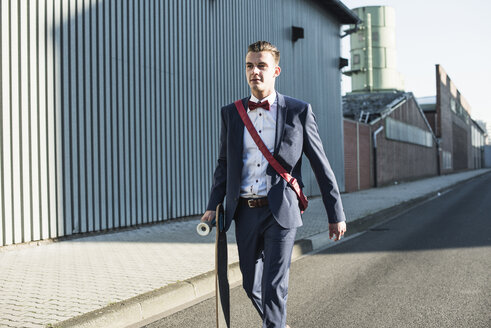 Young businessman walking with skateboard on the street - UUF09825