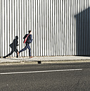 Young businessman running on pavement along building - UUF09828