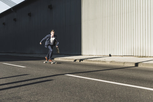 Young businessman riding skateboard on the street - UUF09840