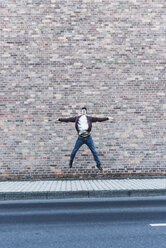 Young man jumping in front of brick wall - UUF09846
