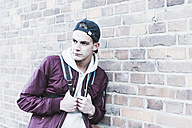 Portrait of young man leaning against brick wall - UUF09849