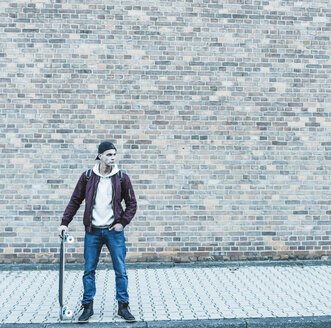 Serious young man with skateboard in front of brick wall - UUF09855