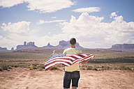 USA, Utah, back view of man with American Flag looking at Monument Valley - EPF00278