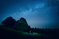 Austria, Mondsee, young man standing on empty street under starry sky - WVF00789