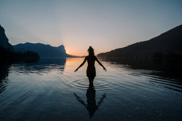 Austria, Mondsee, Lake Mondsee, silhouette of woman standing in water at sunset - WVF00792