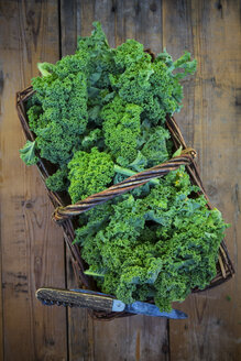 Wickerbasket of kale leaves and pocket knife on wood - LVF05800