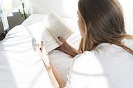 Young woman lying on bed reading book - KKAF00315