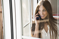 Smiling young woman on the phone at the window - KKAF00327