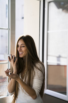 Smiling young woman using cell phone at the window - KKAF00330