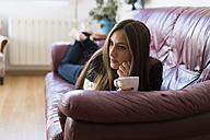 Young woman lying on couch holding cup of coffee - KKAF00339