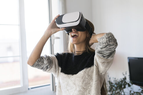 Excited young woman wearing VR glasses at home - KKAF00345