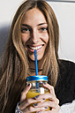 Portrait of smiling young woman drinking homemade drink - KKAF00348