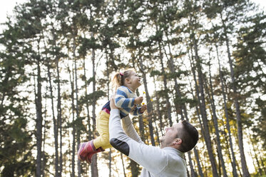 Father lifting up his daughter in forest - HAPF01299
