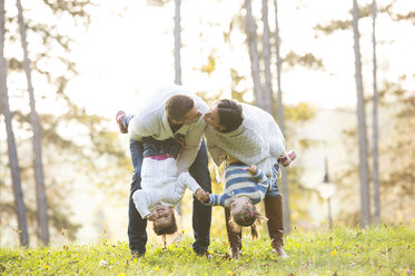Couple kissing and holding their two daughters upside down - HAPF01311
