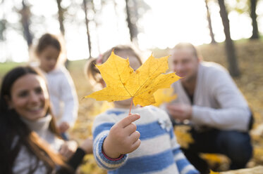 Girl with her family holding autumn leaf - HAPF01314