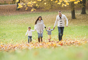 Happy family with two girls walking in autumn leaves - HAPF01323
