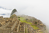 Peru, Andes, Urubamba Valley, Machu Picchu with mountain Huayna Picchu in fog and clouds - FOF08771