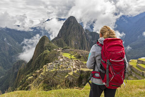 Peru, Andes, Urubamba Valley, tourist with red backpack at Machu Picchu with mountain Huayna Picchu - FOF08776