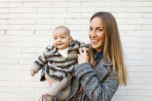 Portrait of happy mother holding baby at brick wall - VABF01030