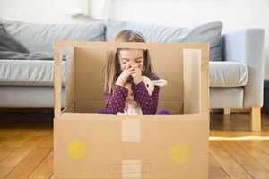 Girl with doll sitting in self-made cardboard car at home - LVF05807