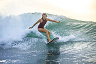 Indonesia, Bali, woman surfing on a wave - KNTF00615