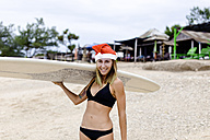 Indonesia, Bali, smiling woman carrying surfboard on the beach wearing Santa hat - KNTF00621