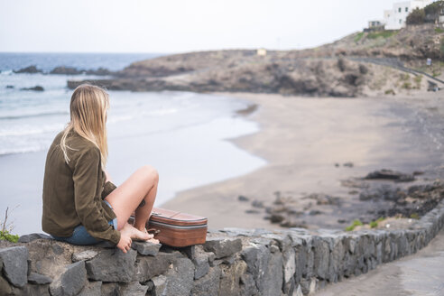 Spain, Tenerife, young blond woman sitting on wall near the beach - SIPF01345