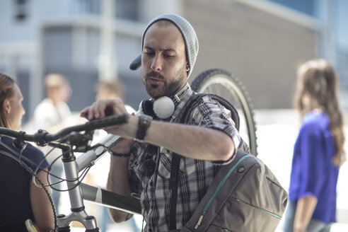 Young man holding bicycle checking the time - ZEF12483