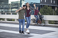 Young man supporting laughing girlfriend on skateboard - ZEF12492