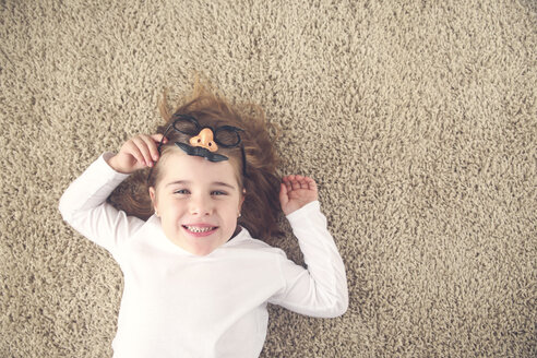 Portrait of little girl lying on the carpet holding funny glasses with plastic nose - RTBF00607