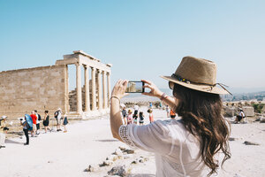 Greece, Athens, woman taking a cell phone picture of the Erechtheion temple in the Acropolis - GEMF01401