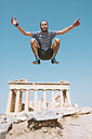 Greece, Athens, man jumping mid-air at the Parthenon temple on the Acropolis - GEMF01407