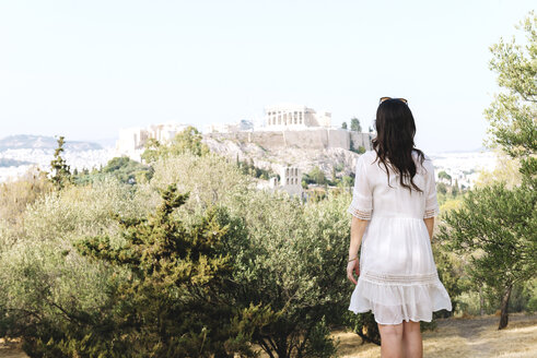 Greece, Athens, woman looking at The Acropolis and Parthenon surrounded by olive trees from Areopagus - GEMF01422