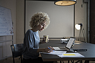 Woman working on laptop and documents in office - RBF05562