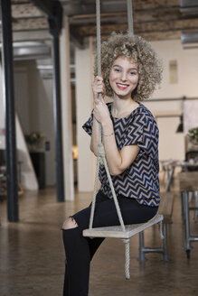 Portrait of smiling woman on swing in modern office - RBF05568