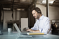Businessman at desk with laptop and headphones - RBF05607