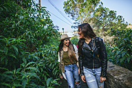 Two happy young women walking on a path with plants - KIJF01109