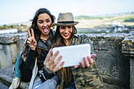 Two happy young women on a trip taking a selfie with a tablet - KIJF01115