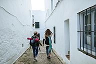 Two young women on a trip walking in a town holding hands - KIJF01118