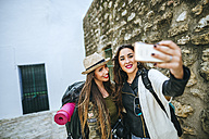 Two happy young women taking a selfie with a smart phone - KIJF01121