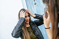 Young woman adjusting her hair looking at a friend's cell phone - KIJF01130