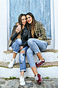 Two smiling young women sitting on stoop hugging - KIJF01133